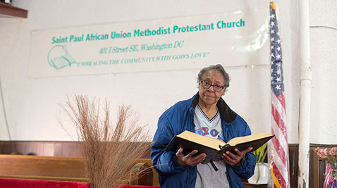 Pastor Willie Mae Footman holds a Bible in front of the altar of the Saint Paul African Union Methodist Protestant Church in Southeast Washington, D.C. The church is part of the African-American denomination that was incorporated in 1813 and is the only surviving church in the Navy Yard area. Capital News Service photo by James Levin.