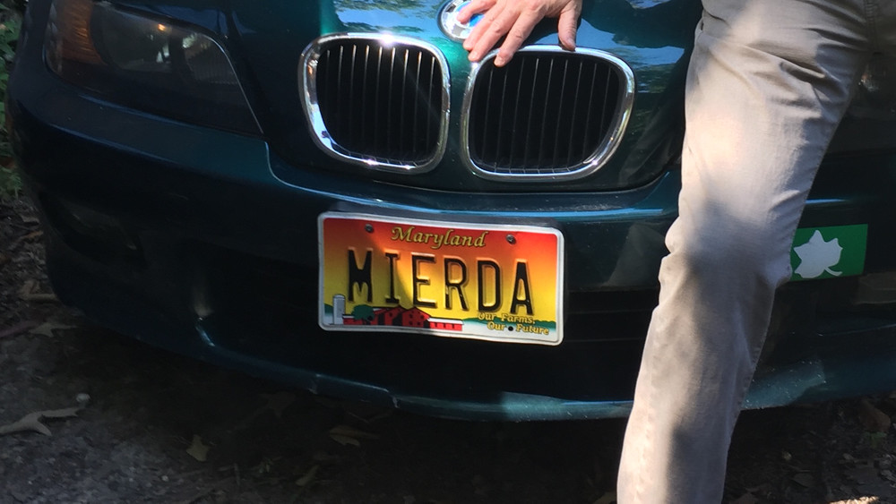 """John T. Mitchell poses with his car's """"MIERDA"""" license plate, which the Maryland Motor Vehicle Administration recalled in 2011. The plate is the subject of a case in the Maryland Court of Appeals. Sept. 14, 2016. (Courtesy photo from John T. Mitchell.)"""
