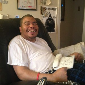 Damon Briggs, 39, cracks a joke in his home in Silver Spring where he lives with his parents. Briggs has moderate to severe cerebral palsy, which affects his ability to walk and grasp small objects, but he explains that it doesn't impact any of his cognitive abilities or social skills, which is why it frustrates him that transportation issues limit his ability to go out into the community. Capital News Service photo by Grace Toohey.
