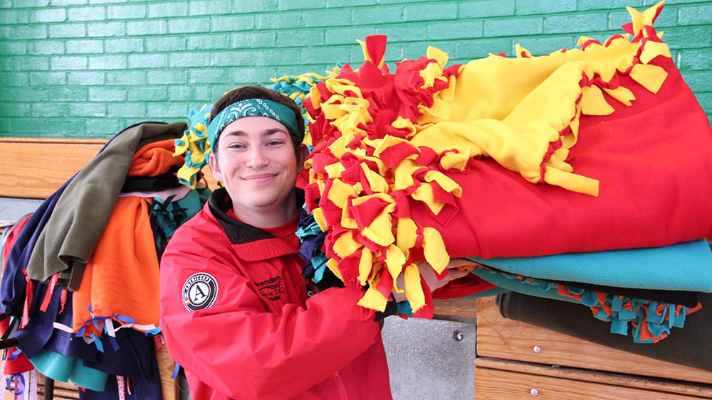 A City Year AmeriCorps member carries blankets created by volunteers at a school in Southeast D.C. as part of the 2016 MLK National Day of Service. Photo courtesy of Corporation for National Community Service