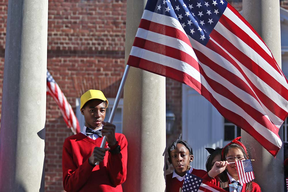 Olukayode Akinpelu Jr., left, a 14-year-old 8th grader at St. Francis, waives a flag at the non-public school advocacy day in Annapolis, Md., on March 2, 2017. Gov. Larry Hogan spoke at the rally in support of using state funds for non-public schools throughout the state. (Hannah Klarner / Capital News Service)