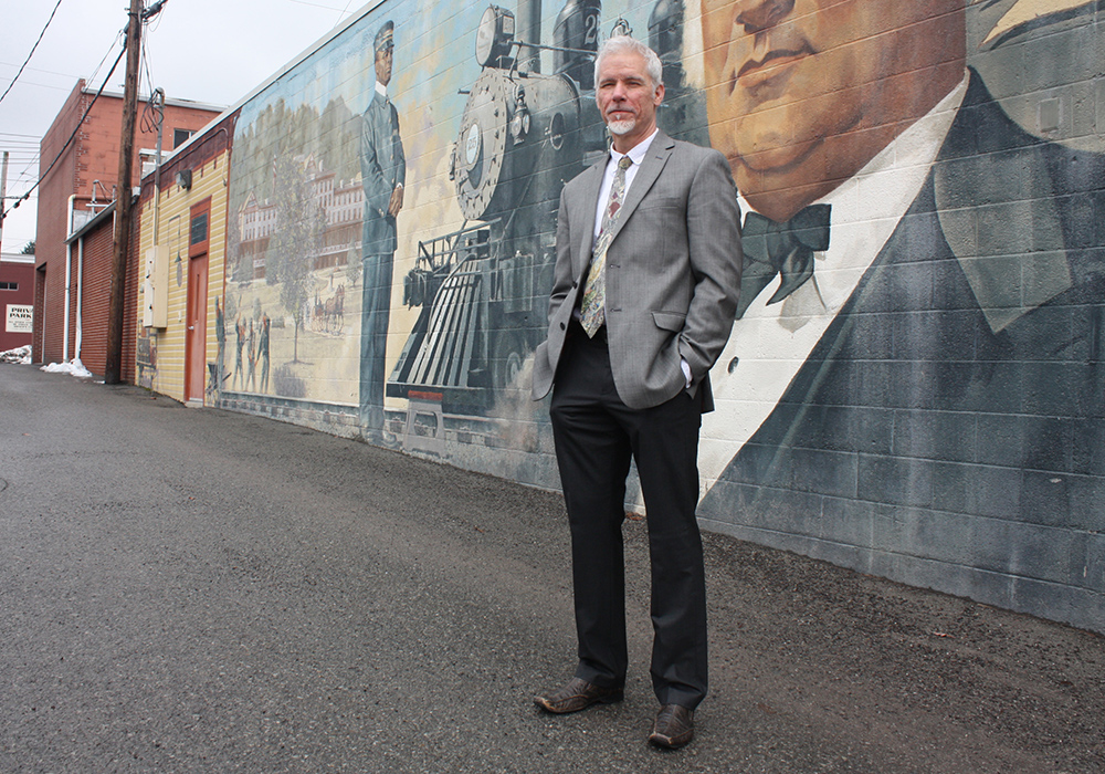 Mark Stutzman, illustrator and president of Engage Mountain Maryland, an anti-fracking group, stands in front of a mural he painted in Oakland, Maryland. (Photo by J.F. Meils/Capital News Service)