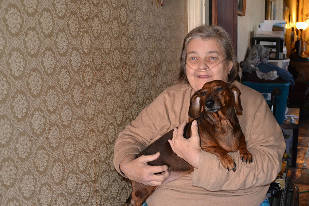 Dawn Ford sits in a first-floor hallway with her dog, Sarge, who catches the mice that come into her South Smallwood Street home. (Capital News Service photo by Abby Mergenmeier)