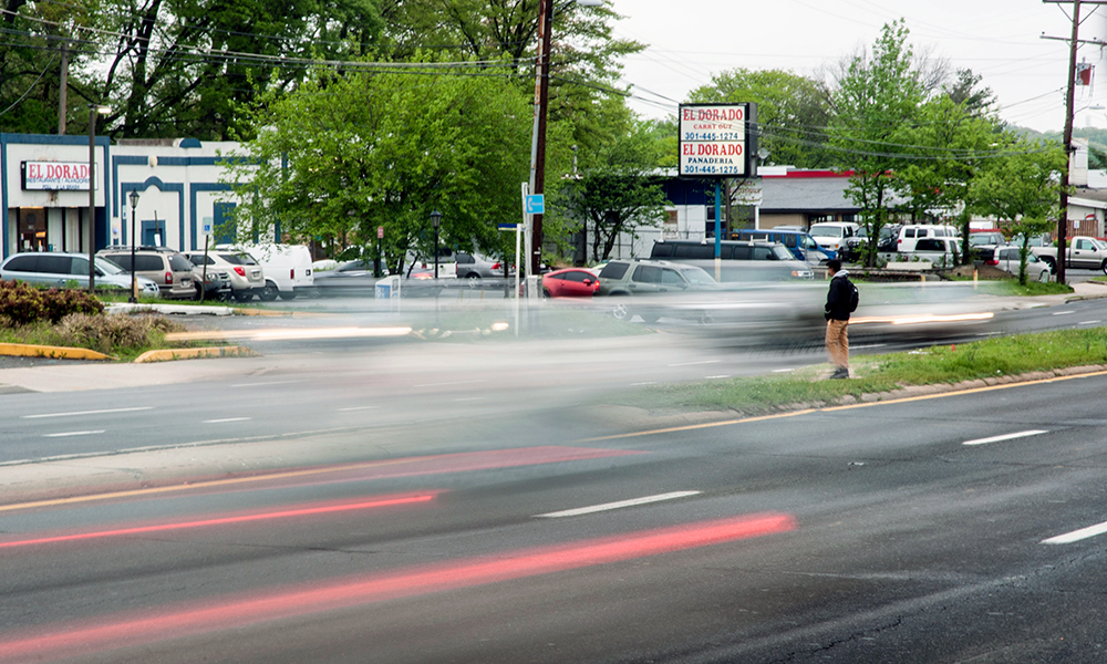 A man looks for a break in traffic to cross University Boulevard in Langley Park. In the past eight years, at least 138 pedestrians have been hit and eight have died on a two-mile stretch of the state highway that runs through the low-income, immigrant community outside Washington, D.C. (Capital News Service photo by Rebecca Rainey)
