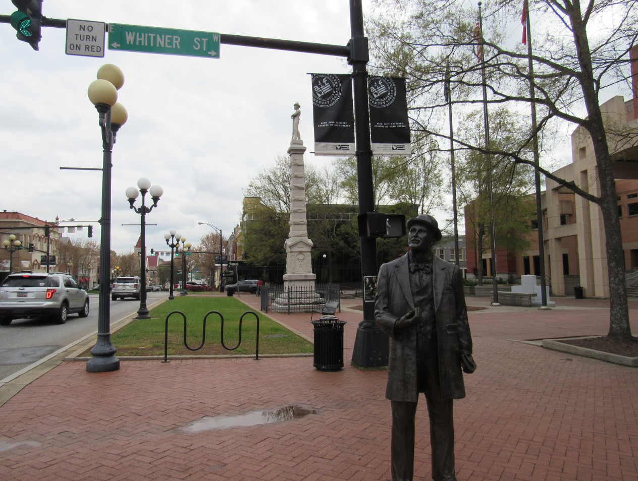 A statue of William C. Whitner, an engineer who helped bring electricity to Anderson, stands in front of a 35-foot Confederate statue. Both are located in front of the Anderson County Courthouse in Anderson City, South Carolina. Capital News Service photo by Lindsey Feingold.