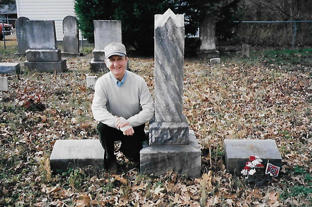 LTC John P. Zebelean III (ret.) posing next to the grave of relative Private Matthew J. Ham, 2nd Regiment, North Carolina Junior Reserves (1861-1865). The plot is located on his family's former property in Wayne County, NC. Zebelean's ancestors and five of their slaves are buried here. Photo Courtesy LTC John P. Zebelean III.