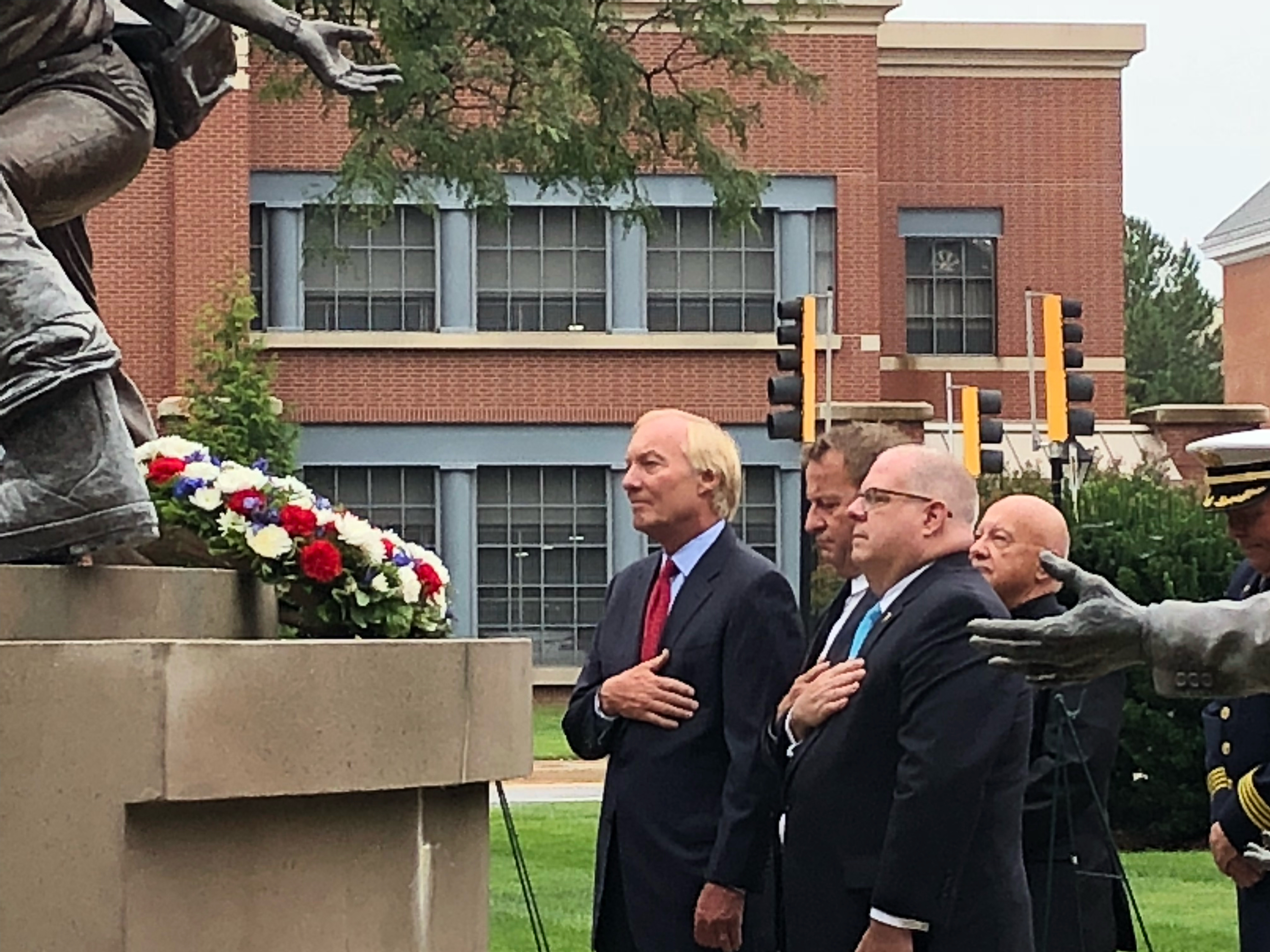 Maryland Gov. Larry Hogan, Annapolis Mayor Gavin Buckley and Maryland Comptroller Peter Franchot stand for a moment of silence before the Maryland Fire-Rescue Services Memorial during a wreath-laying ceremony commemorating the 17th anniversary of the Sept. 11, 2001, terrorist attacks on Sept. 11, 2018, in Annapolis, Maryland. (Photo by Brooks DuBose/Capital News Service)