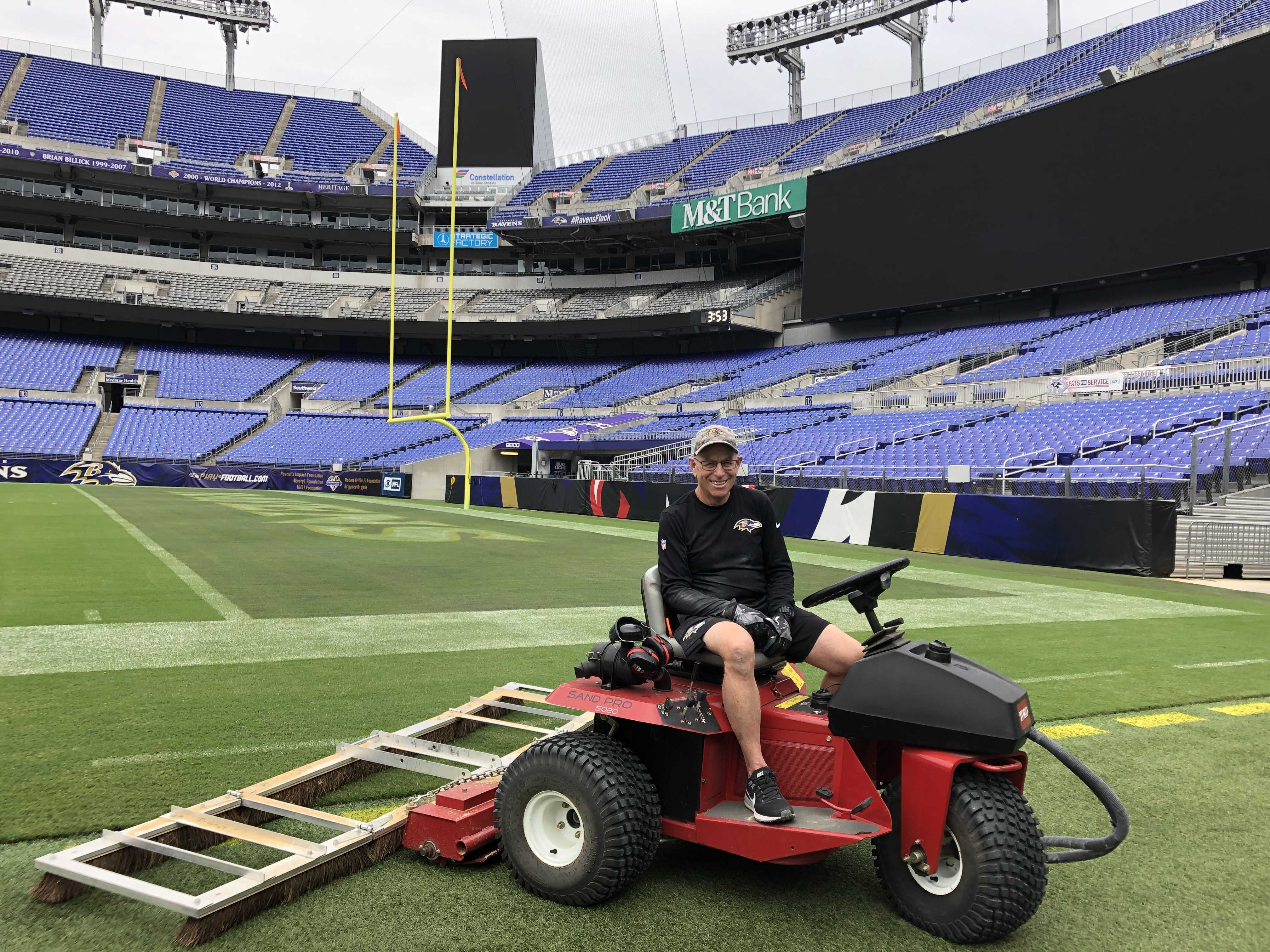 Baltimore Ravens groundskeeper Don Follett brushes rye grass seed into the turf at M&T Bank Stadium in Baltimore in September.Follett said extreme weather is something he grapples with. (Andy Kostka/Capital News Service)