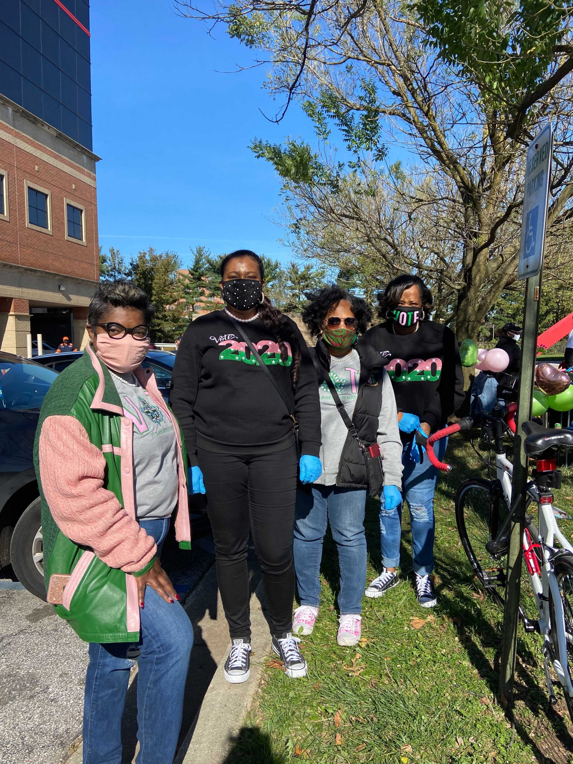 """Nicole Wallace, left in pink and green, is here helping her daughter, who founded """"Baltimore Votes"""" which strives to increase black voter turnout."""