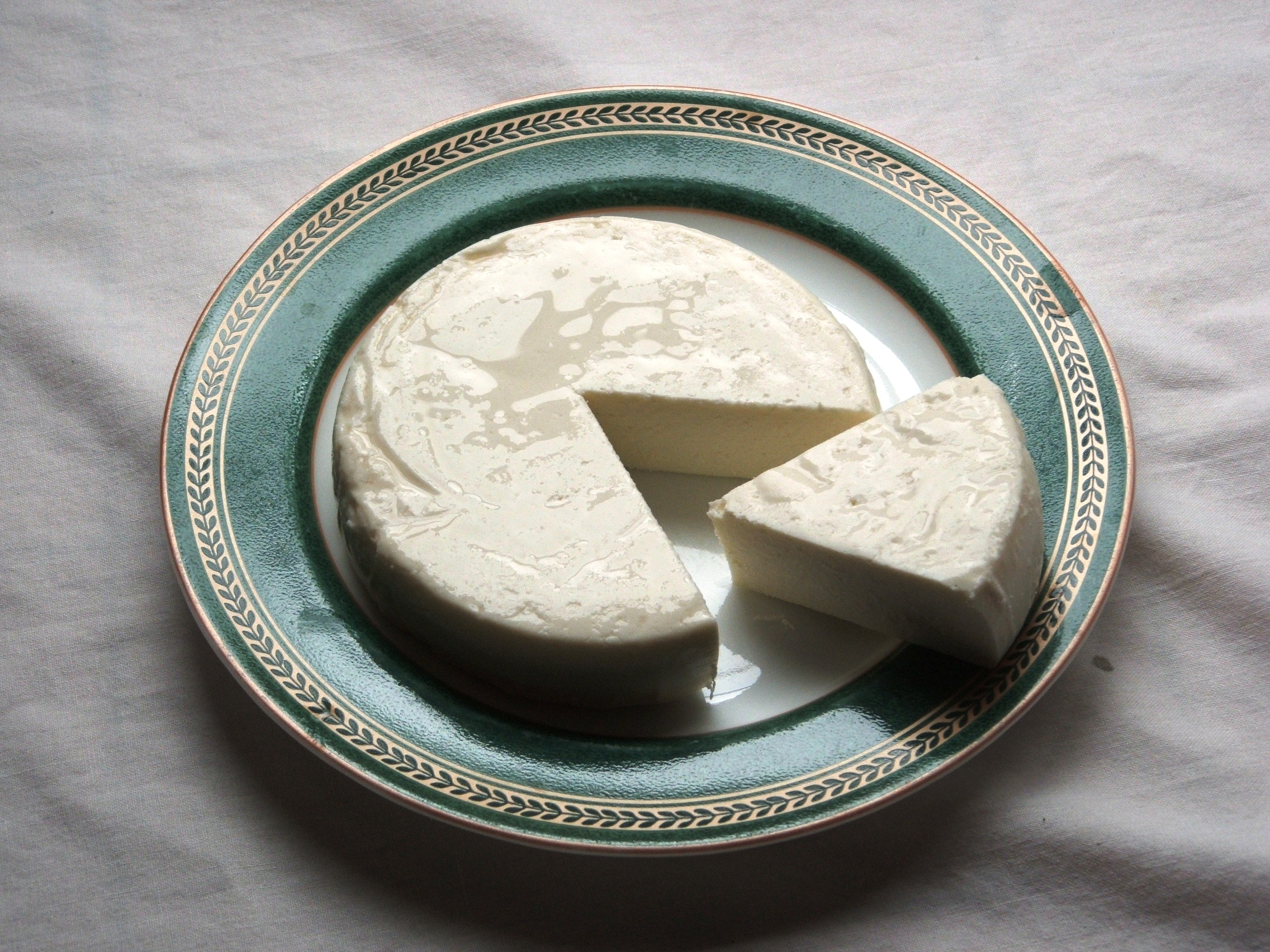 Queso fresco on a plate, one slice removed