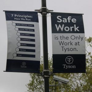 Banners displaying Tyson's work principles hang above a surveillance camera in the employee parking lot at the Berry Street location in Springdale, Arkansas, on April 20, 2021. (Photo by Abby Zimmardi)