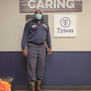 Eric Brown, 51, stands in his Tyson uniform, which includes a medical mask, at the Tyson plant in Hope, Arkansas, April 21, 2021. Brown is a night-shift maintenance worker who has felt safe from contracting COVID-19 while at work because of safety procedures that Tyson management enforces. (Photo courtesy of Eric Brown)