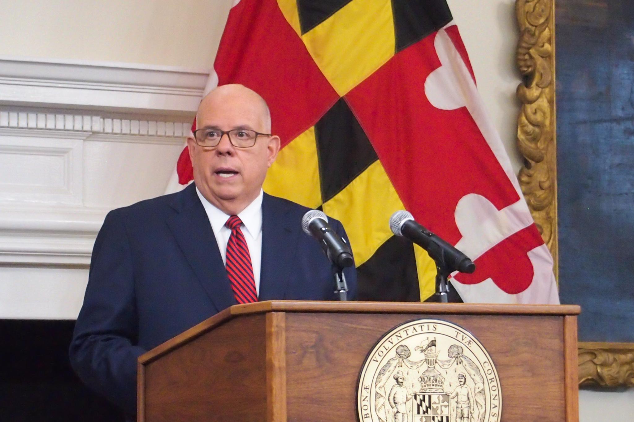 Hogan stands at a podium